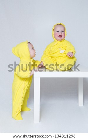 Two kids in yellow suits - stock photo