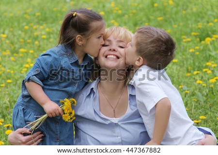 Two kids kissing mother among dandelion field