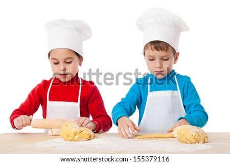 Two kids kneading the dough together, isolated on white - stock photo