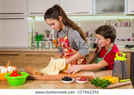 Two kids kneading the thin sheet of  dough on table, making the pizza together in the kitchen interior