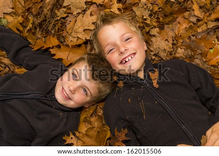 two kids laying in a pile of leaves - stock photo