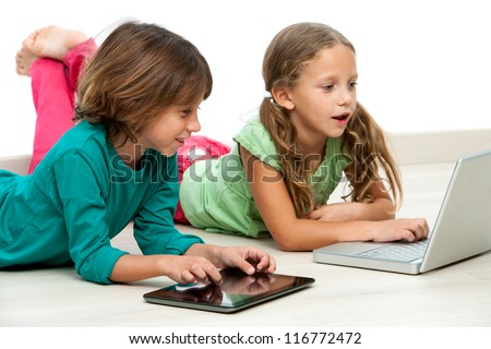 Two kids laying on floor with laptop and digital tablet. - stock photo