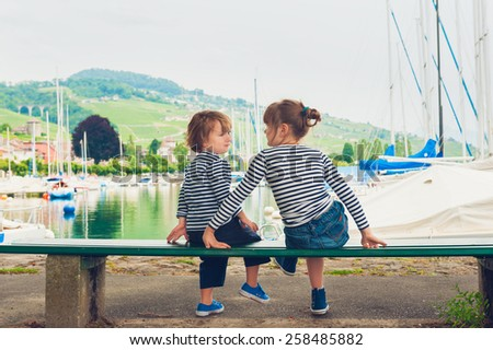 Two kids, little girl and boy resting by the lake, wearing frocks and blue shoes - stock photo