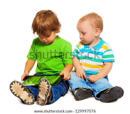 Two kids - little two years old playing with tablet computer - stock photo