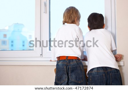 two kids looking at window - stock photo