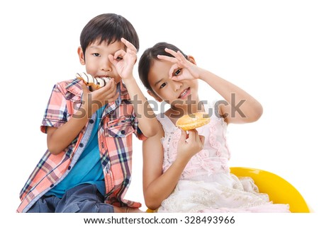 Two kids looking through their ok finger with donuts - stock photo