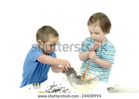 Two kids make chocolate chip cookies - stock photo