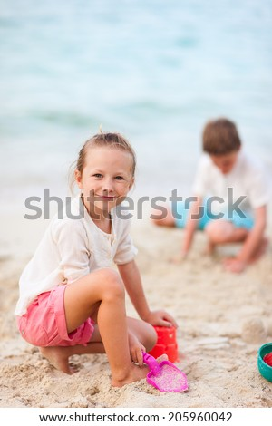 Two kids making sand castle and playing at tropical beach