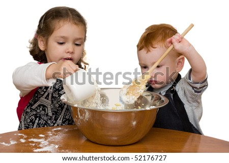 Two kids measuring and mixing into large mixing bowl. Isolated on white.