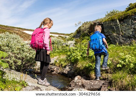 Two kids on a hike wearing their backpacks and exploring nature in Norway on a sunny day with remains of snow in the background.