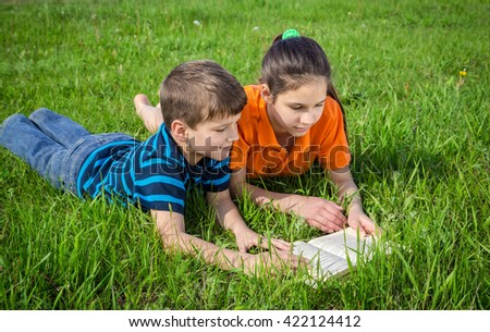 Two kids on green grass meadow reading the book together
