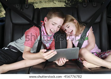 Two Kids on Technology in the back of a car