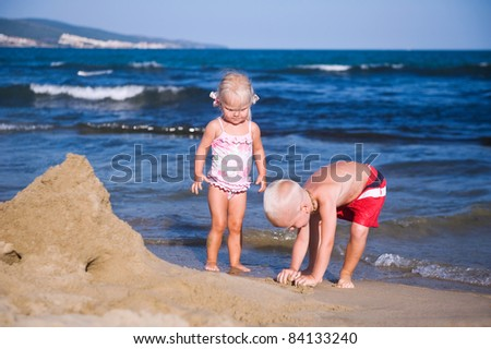 Two kids on the beach building sandcastles - stock photo