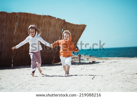 Two kids playing at the beach - stock photo