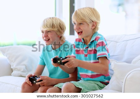 Two kids playing video game at home. Twin teenage brothers having fun after school day laughing and holding joysticks in hands sitting on white sofa in bright sunny living room with big windows - stock photo