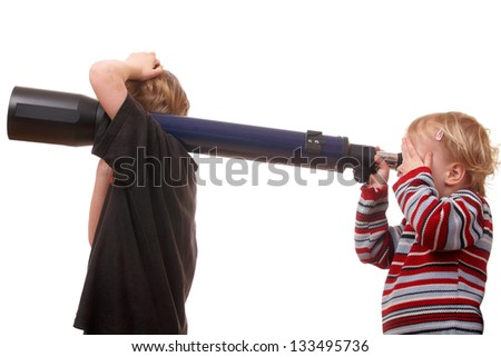 Two kids playing with a telescope on white background - stock photo