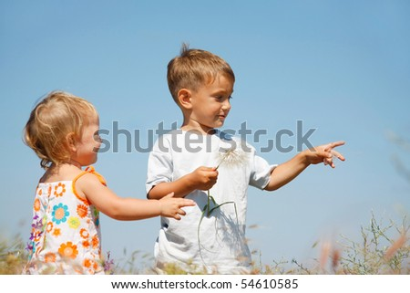 two kids playing with big dandelions - stock photo