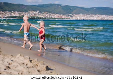 Two kids running along the beach - stock photo