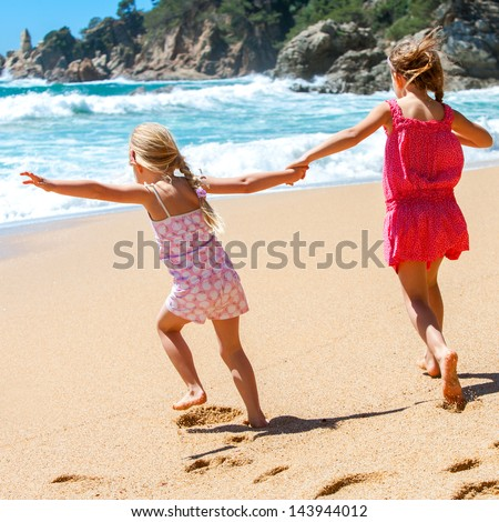 Two kids running towards water at seaside.