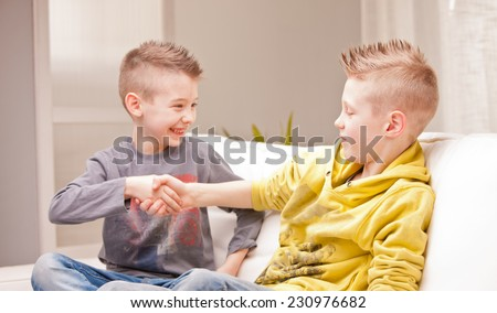 two kids shaking their hands as like as they were businessmen - stock photo