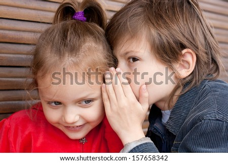two kids sharing secret - stock photo