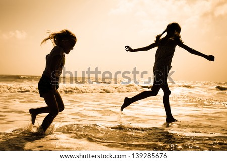 two kids silhouettes running on beach at sunset - stock photo