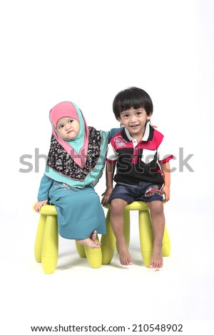 two kids sitting on the chair holding hand together