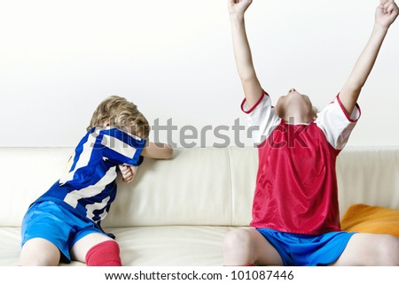 Two kids supporting different teams watching football and celebrating at home. - stock photo