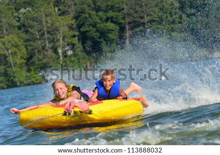 two kids trying not to fall off a water tube - stock photo