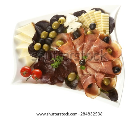Two kinds of smoked ham and three kinds of cheese served on a white plate with olives and cherry tomatoes. Isolated on white. - stock photo