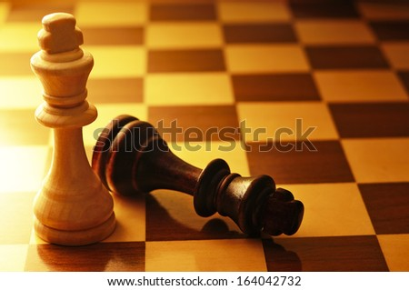 Two King chess pieces on a chessboard with the dark king lying on its side at the foot of the victorious light wood King, conceptual image with copyspace - stock photo