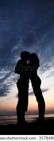 Two kissing at sunset - stock photo
