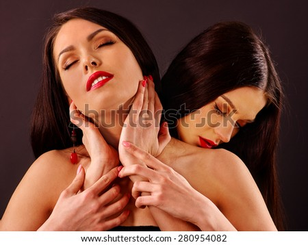Two kissing lesbian women with closed eyes kissing .Grey background. - stock photo