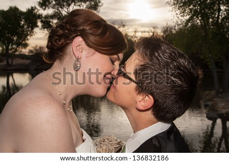 Two kissing newlywed lesbians outside near pond - stock photo