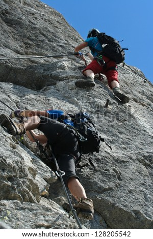 Two klettersteig climbers at steep wall - stock photo