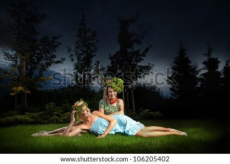 Two ladies in gorgeous garden - stock photo