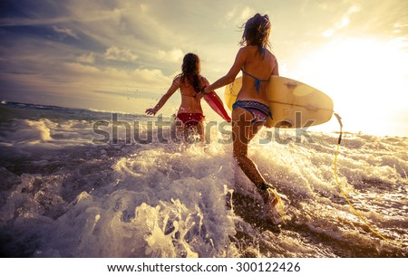 Two ladies running into the sea with surf boards - stock photo