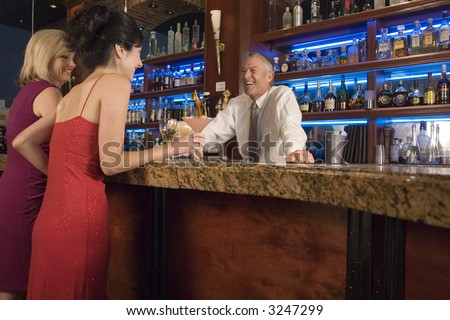Two ladies talk to a bartender at the bar