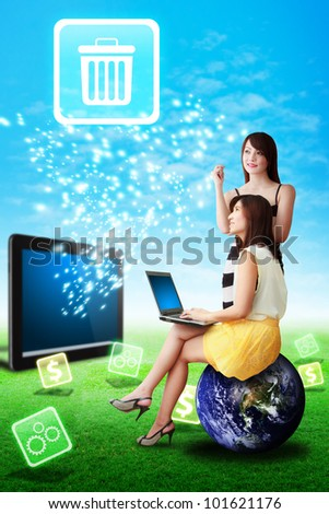Two lady look at the bin icon from tablet computer on the grass field : Elements of this image furnished by NASA - stock photo