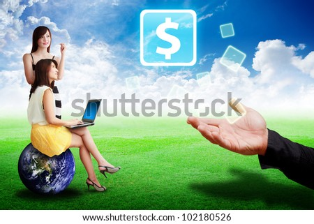 Two lady look at the Money icon from the smart hand : Elements of this image furnished by NASA - stock photo