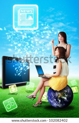 Two lady look at the news icon from touch pad : Elements of this image furnished by NASA - stock photo