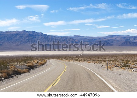 Two lane highway passing through desert flatland with mountains in background. Horizontal shot.