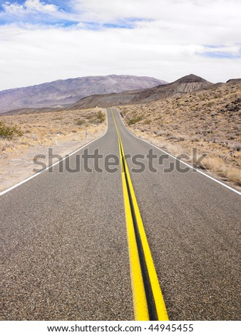 Two lane highway passing through desert with mountains in background. Horizontal shot.