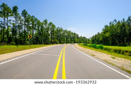 Two lane rural highway curves along a pine tree forest. - stock photo