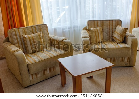 Two large chair in beige brown stripes near there is a small wooden table in the background and large windows with white curtains - stock photo
