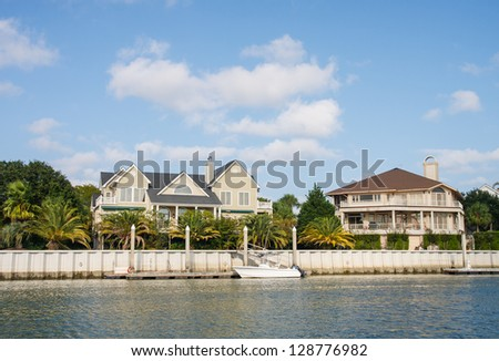 Two large coastal homes with a small boat tied to pier - stock photo