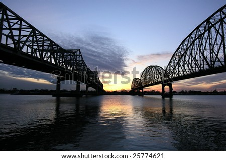 Two large historic bridges cross a wide river in Louisiana. - stock photo