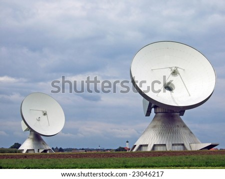 Two large satellite dishes on a field in Bavaria, Germany - stock photo