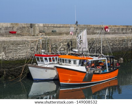 two large working boats in annalong harbor - stock photo