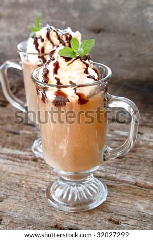 Two latte's with whipped topping and chocolate syrup and garnished with fresh mint leaves. - stock photo
